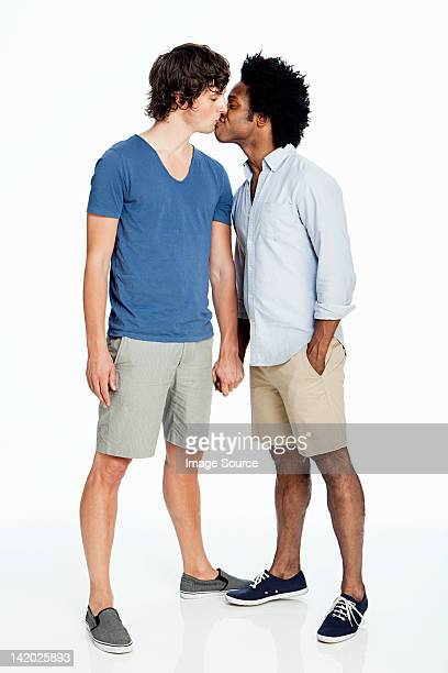 Gay couple kissing against white background