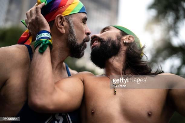 couple gay s'embrasser sur la gay parade - gay love photos et images de collection