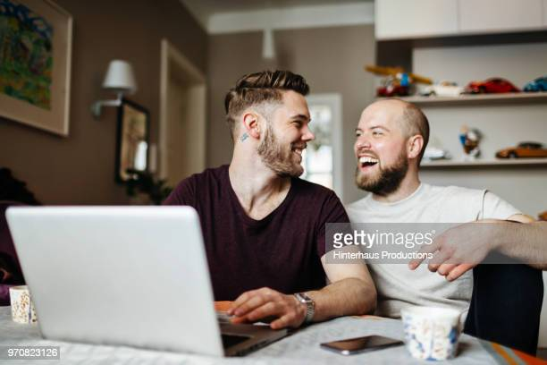 Gay Couple Laughing While Looking At Photos Together
