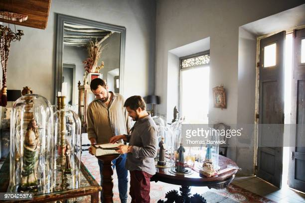 Gay couple looking at artifacts in boutique while on vacation