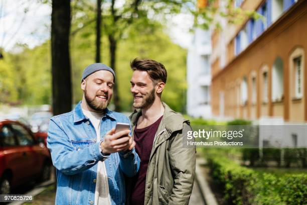 Gay Couple Looking At Map On Smartphone Together.