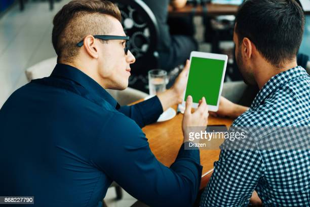 Gay couple looking for travel destinations on digital tablet with green screen