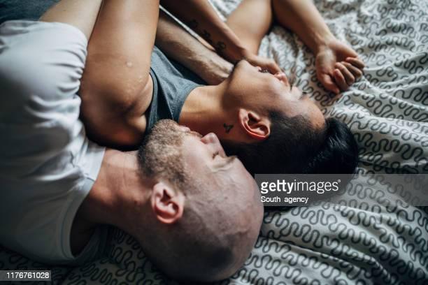 couples gais se trouvant dans le lit et faisant la sieste - beautiful gay men photos et images de collection