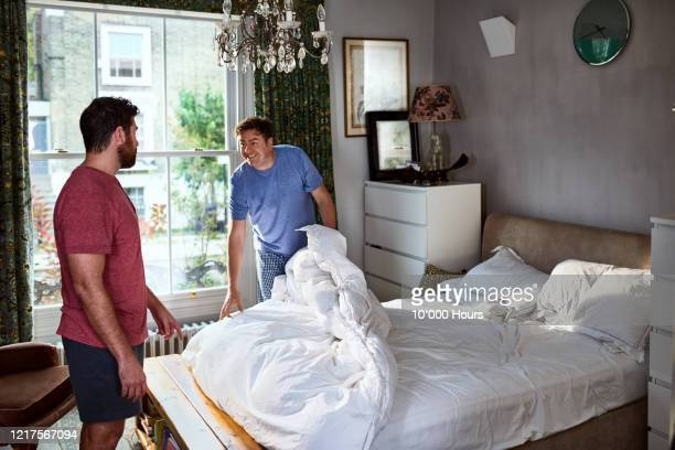 gay couple making bed in stylish bedroom - cleaning stock pictures, royalty-free photos & images