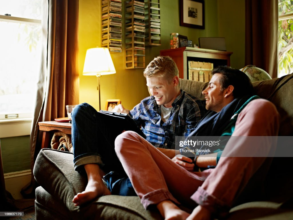 Gay couple on couch looking at digital tablet : Stock Photo