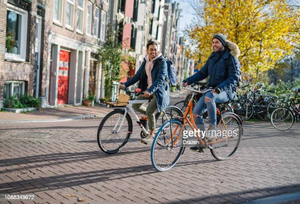gay couple on rent-a-bikes - indonesian and european men are in relationship and spending time on city break - bonding stock pictures, royalty-free photos & images