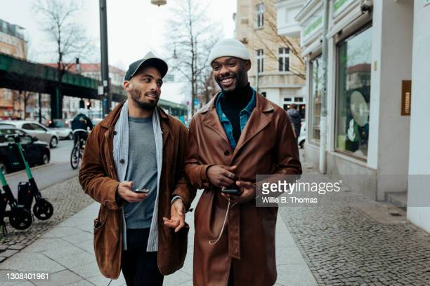 gay couple on their way to eat some food together - beautiful gay men photos et images de collection