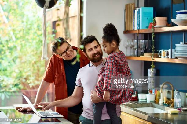 gay couple online shopping with their daughter - parent stock pictures, royalty-free photos & images