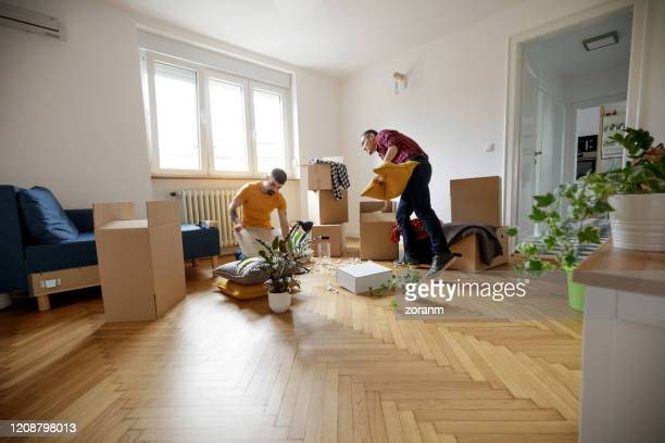 gay couple opening boxes together in their new home - wide angle stock pictures, royalty-free photos & images