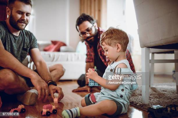 gay couple playing with adopted baby son and his toys - parent stock pictures, royalty-free photos & images