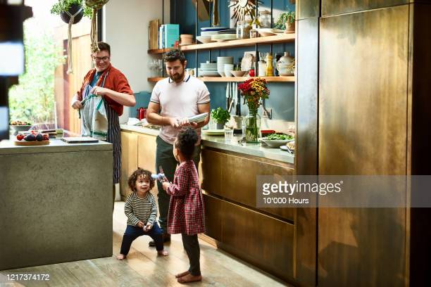 gay couple preparing dinner with young children in kitchen - sunday stock pictures, royalty-free photos & images