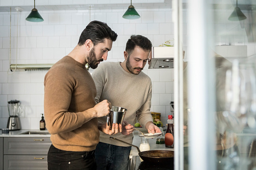 Gay couple preparing food in kitchen at home - gettyimageskorea