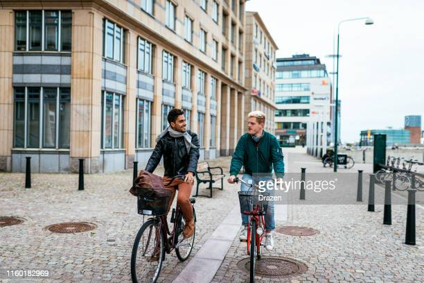 gay couple riding bicycles - malmo stock pictures, royalty-free photos & images