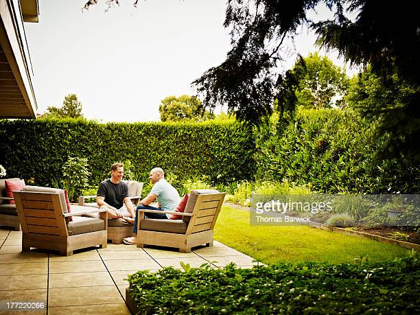 gay couple seated together on backyard patio - courtyard stock pictures, royalty-free photos & images