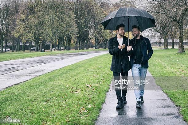 Gay couple sharing an umbrella