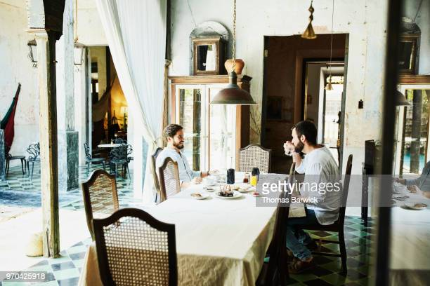 Gay couple sharing breakfast in courtyard of boutique hotel