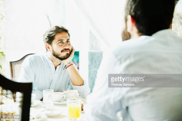 Gay couple sharing breakfast together while on vacation