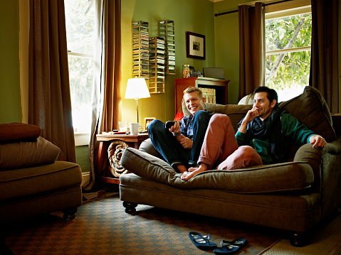 Gay couple sitting on couch in home watching TV - gettyimageskorea
