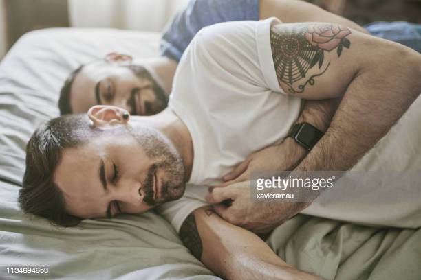 gay couple sleeping on bed at home - gay man stock pictures, royalty-free photos & images