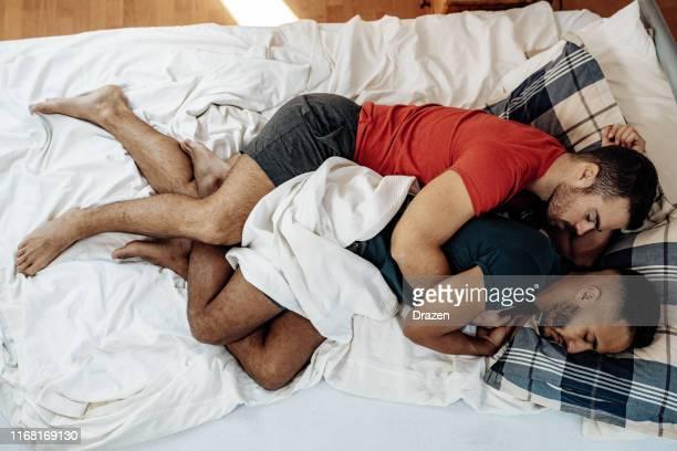 coppia gay che dorme insieme a letto in posizione cucchiaio - abbracciarsi a letto foto e immagini stock