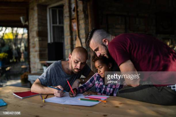 Gay couple spending creative time with their daughter