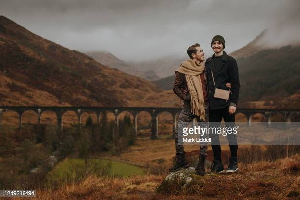 gay couple standing in front of glenfinnan viaduct in the highlands of scotland - couple relationship stock pictures, royalty-free photos & images