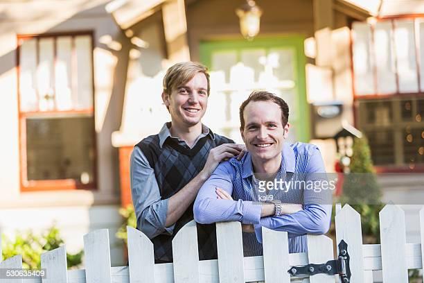 Gay couple debout en face de la maison