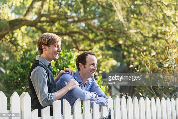 Gay couple standing in front yard