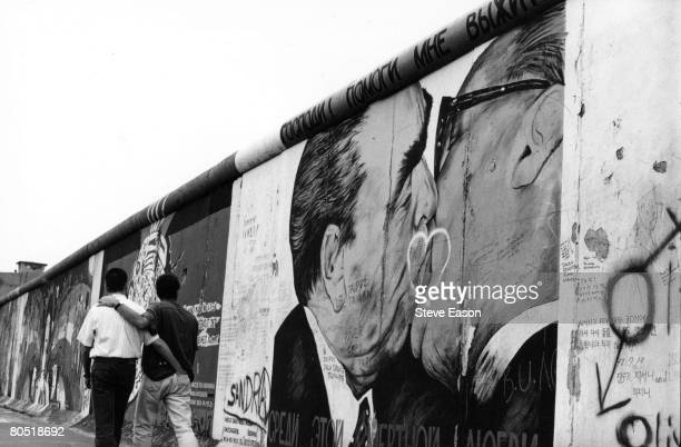 A gay couple strolling past graffiti on the Berlin Wall depicting German leaders Leonid Brezhnev and Erich Honecker sharing a kiss August 1993