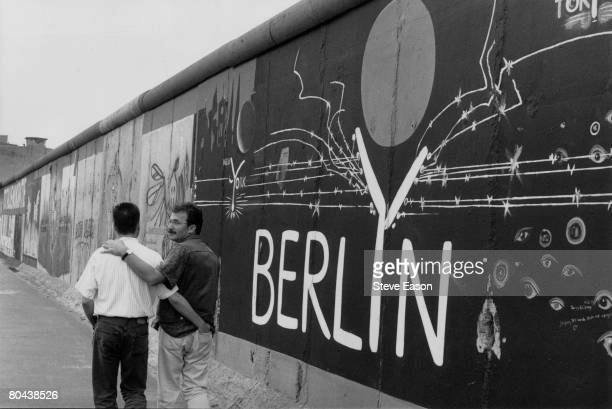 A gay couple strolling past the graffiti on a remaining section of the Berlin Wall August 1993
