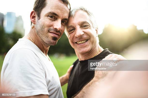 gay couple take a selfie on the park - gay man stock pictures, royalty-free photos & images