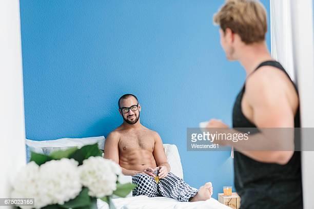 Gay couple talking in bedroom