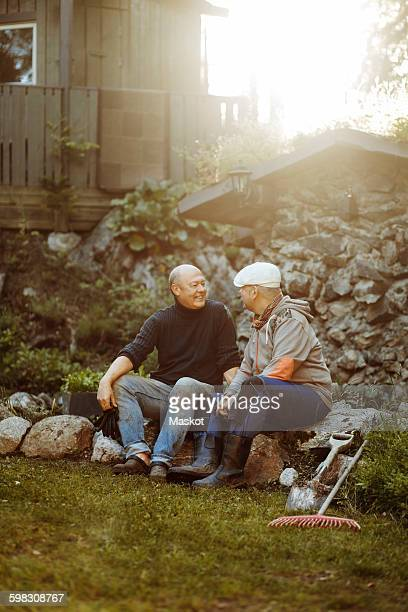 Gay couple talking while sitting on rocks at field