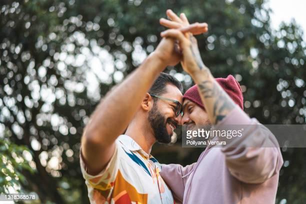 casal gay tocando as mãos no parque público - direitos dos gays - fotografias e filmes do acervo