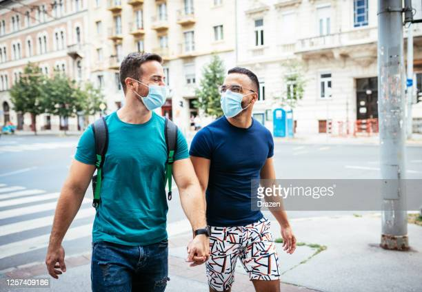 gay couple traveling together and wearing face masks - hungary stock pictures, royalty-free photos & images