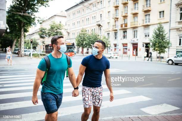 couples gais voyageant ensemble et portant des masques de visage - beautiful gay men photos et images de collection