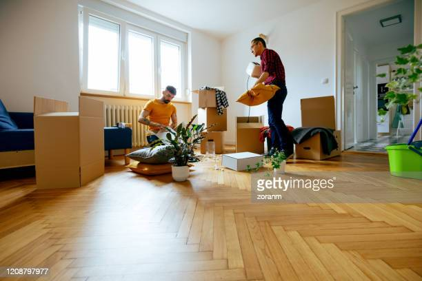 gay couple unpacking together in their new home - toaster appliance stock pictures, royalty-free photos & images