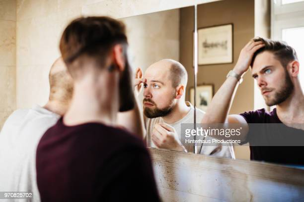 Gay Couple Using Bathroom Mirror Together