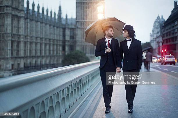 Gay couple walking in London rain.