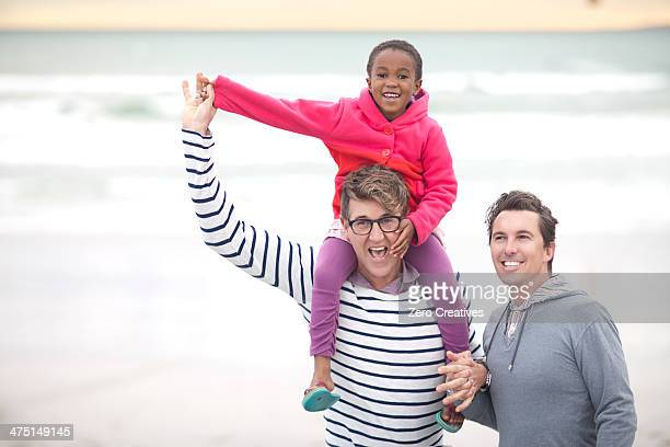 Gay couple walking on beach with child on shoulders