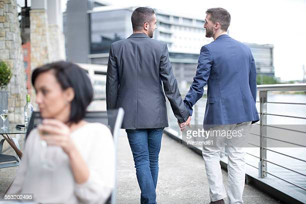Gay couple walking together hand in hand