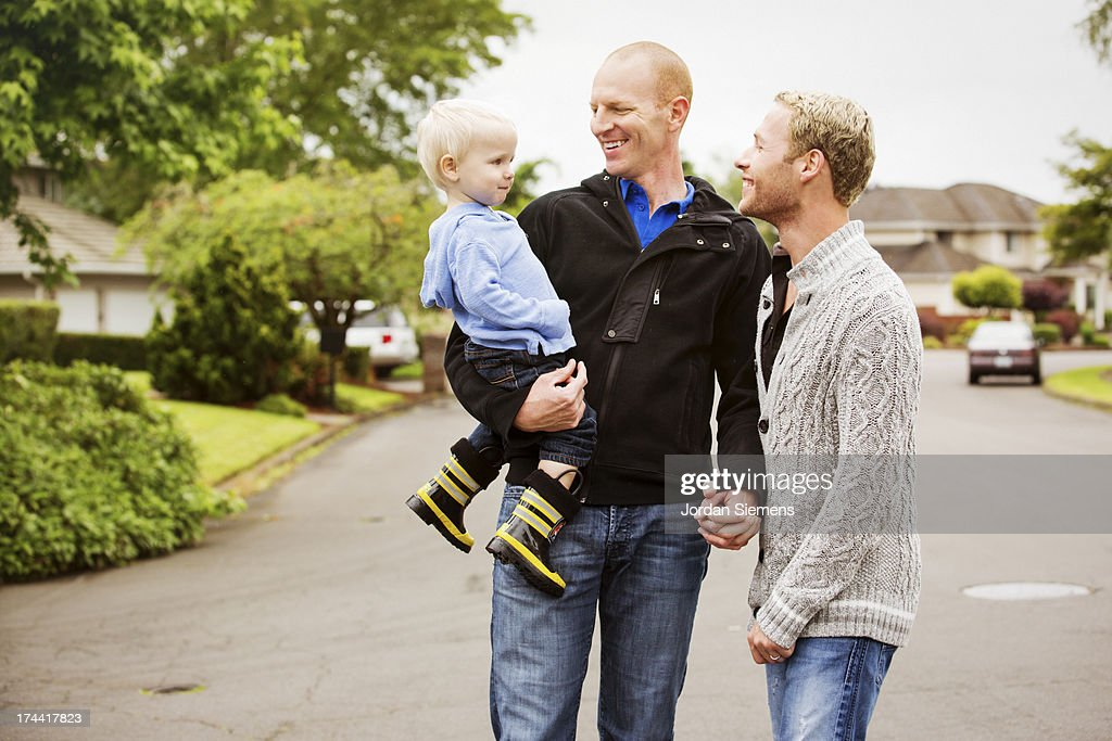 A gay couple walking with their son. : Stock Photo