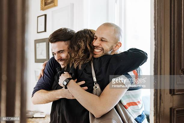 gay couple welcoming their mother at the door - three people stock pictures, royalty-free photos & images