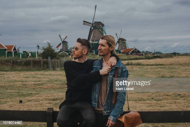Gay couple with arms around one another in front of windmills in Zaanse Schans