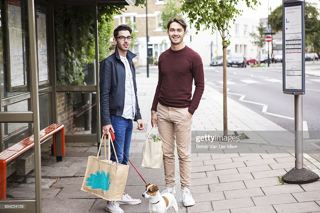 gay couple with dog and shopping waiting for bus. : Stock Photo
