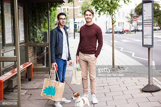 gay couple with dog and shopping waiting for bus.