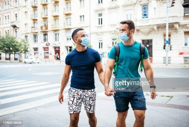 ロックダウン中に街の屋外でフェイスマスクを持つゲイのカップル - social justice concept ストックフォトと画像