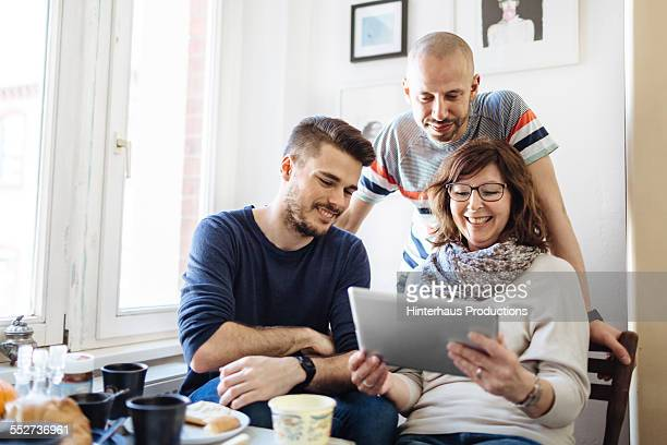 gay couple with their mother at breakfast - gay seniors photos et images de collection