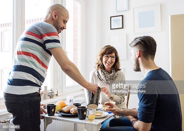 gay couple with their mother having breakfast - gay seniors photos et images de collection