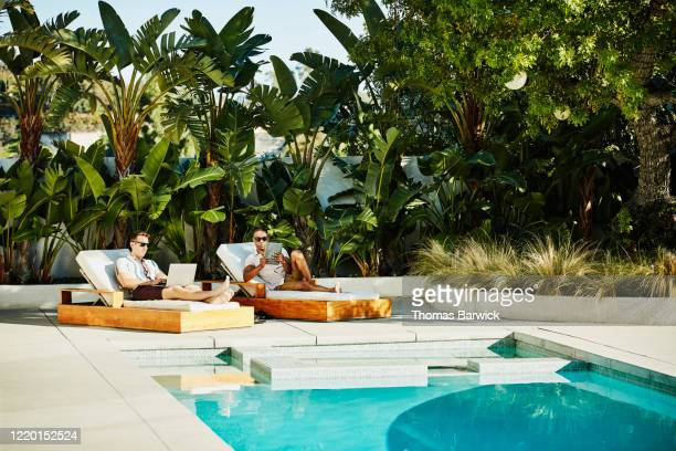 gay couple working on laptop and digital tablet while relaxing by pool - travel photos et images de collection